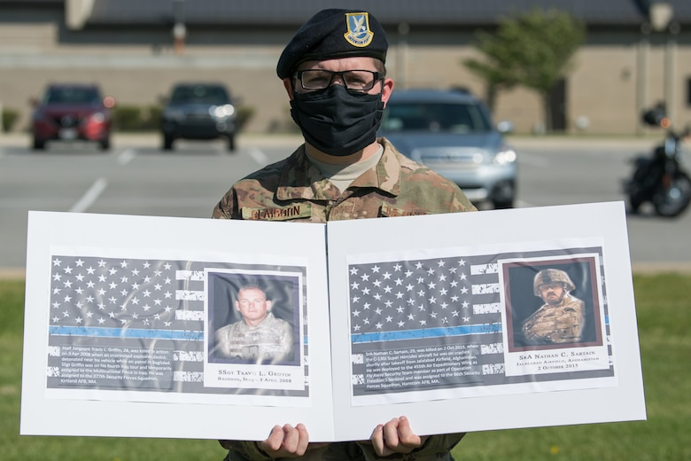Senior Airman Ryan Claiborn, 436th Security Forces Squadron installation patrolman, holds photos of two fallen defenders during a retreat ceremony on Peace Officers Memorial Day May 15, 2020, at Dover Air Force Base, Delaware. The ceremony commemorating fallen military and civilian law enforcement officers marked the end of National Police Week 2020. (U.S. Air Force photo by Mauricio Campino)