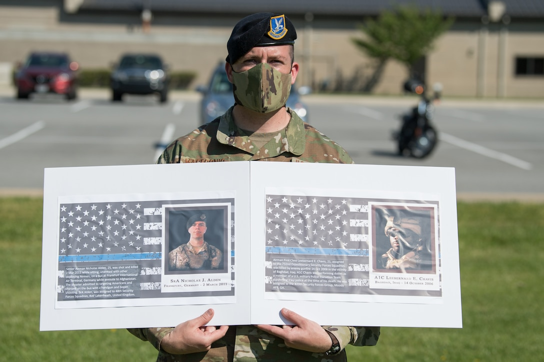 Master Sgt. Justin Macedonio, 436th Security Forces Squadron chief of standardization and evaluation, holds photos of two fallen defenders during a retreat ceremony on Peace Officers Memorial Day May 15, 2020, at Dover Air Force Base, Delaware. The ceremony commemorating fallen military and civilian law enforcement officers marked the end of National Police Week 2020. (U.S. Air Force photo by Mauricio Campino)