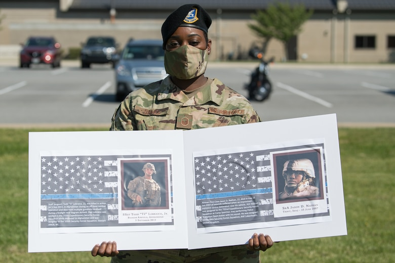Master Sgt. Ashley Daniel, 436th Security Forces Squadron flight chief, holds photos of two fallen defenders during a retreat ceremony on Peace Officers Memorial Day May 15, 2020, at Dover Air Force Base, Delaware. The ceremony commemorating fallen military and civilian law enforcement officers marked the end of National Police Week 2020. (U.S. Air Force photo by Mauricio Campino)