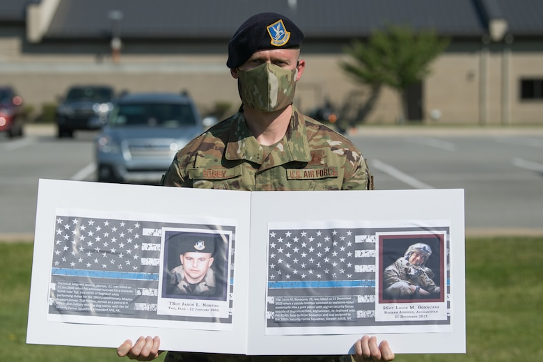 Master Sgt. Jeffrey Robey, 436th Security Forces Squadron noncommissioned officer in charge of investigations, holds photos of two fallen defenders during a retreat ceremony on Peace Officers Memorial Day May 15, 2020, at Dover Air Force Base, Delaware. The ceremony commemorating fallen military and civilian law enforcement officers marked the end of National Police Week 2020. (U.S. Air Force photo by Mauricio Campino)