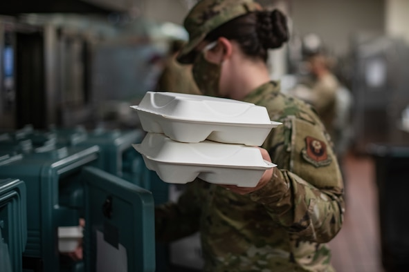 Staff Sgt. Megan Bales, a food services specialist assigned to the 27th Special Operations Force Support Squadron, loads meal containers into insulated boxes at the Pecos Trail Dining Facility on Cannon Air Force Base, N.M, May 15, 2020. The meals were prepared for delivery to Airmen quarantined on the base due to the COVID-19 pandemic. (U.S. Air Force photo by Senior Airman Maxwell Daigle)