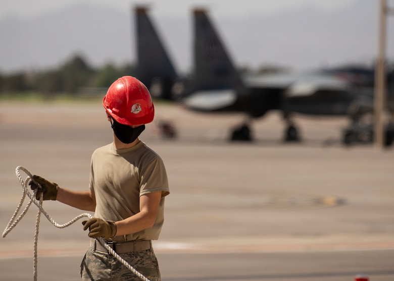 A RED HORSE Airman bundles up rope.