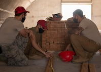 Two RED HORSE Airmen watch as another RED HORSE Airman uses a measuring tape to measure a piece of wood.