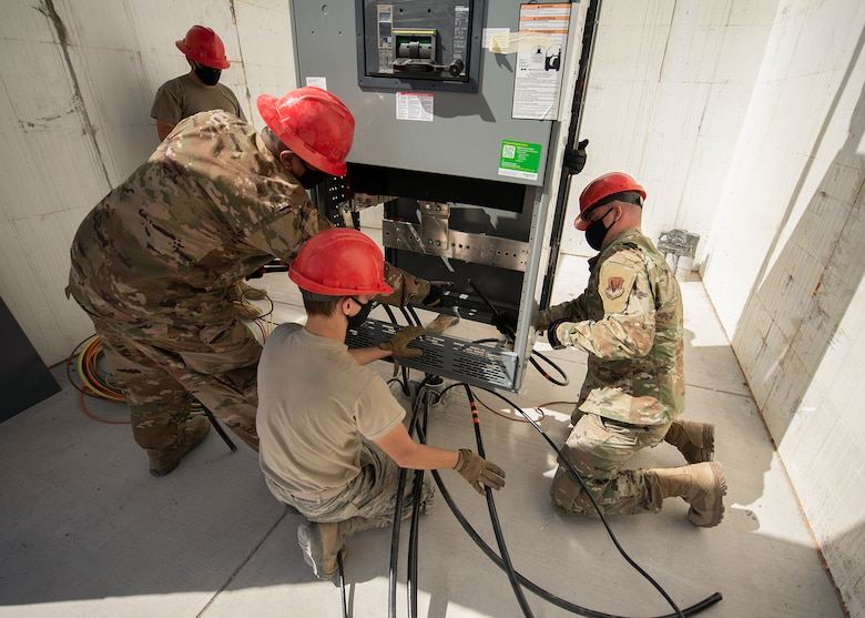 Four RED HORSE Airmen guide a gearbox into position.