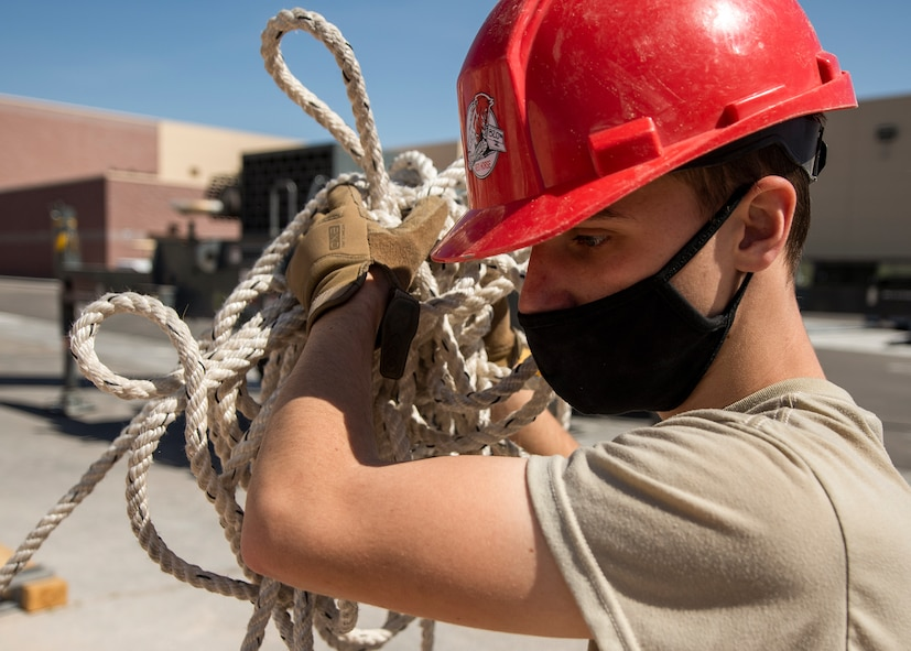 A RED HORSE Airman carries rope over his shoulder.