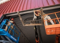 RED HORSE Airmen utilize heavy equipment to install a roll-up door.