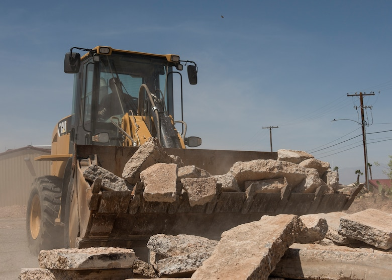 A RED HORSE Airman utilizes a loader to lift and move rocks.