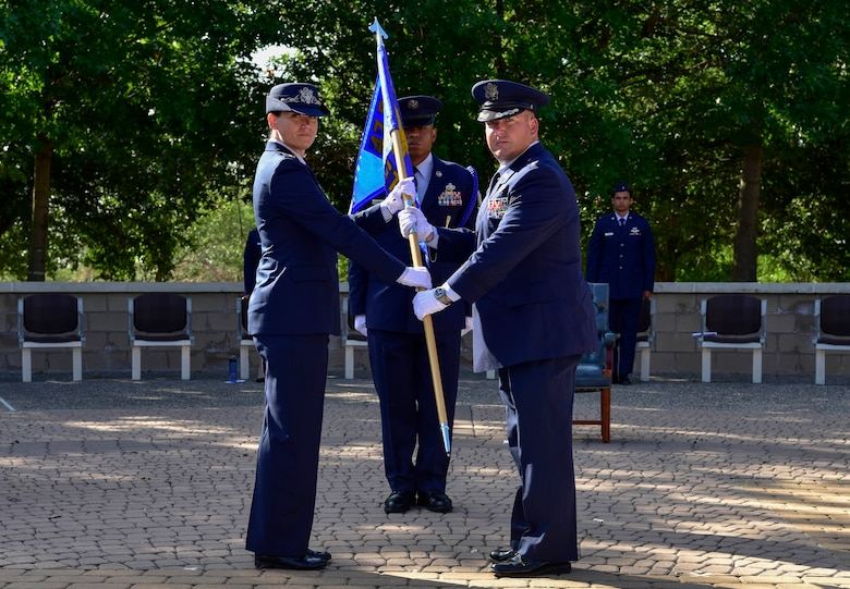 Col. Carey Jones, 47th Operations Group commander, passes a guidon to the new commander of the 47th Student Squadron, Lt. Col. Christopher Best, during a change of command ceremony at Laughlin Air Force Base, Texas, May 18, 2020. The passing of the guidon represents a formal transfer of authority and responsibility from one commander to the next. (U.S. Air Force photo by Senior Airman Marco A. Gomez)