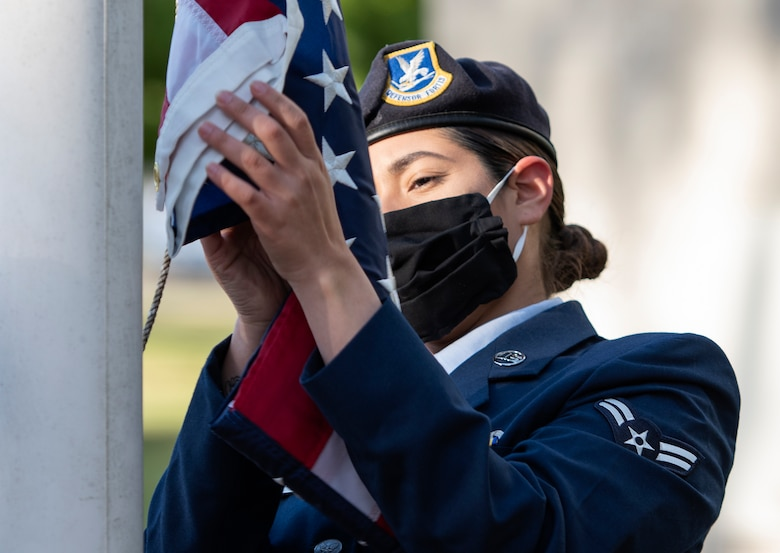 Airman 1st Class Gabbie Reyes, 100th Security Forces Squadron, begins to raise the U.S. flag during the opening ceremony to commemorate the start of National Police Week at RAF Lakenheath, England, May 11, 2020. Established by a joint resolution of Congress in 1962, National Police Week pays special recognition to those law enforcement officers who've lost their lives in the line of duty for the safety and protection of others. (U.S. Air Force photo by Airman 1st Class Jessi Monte)