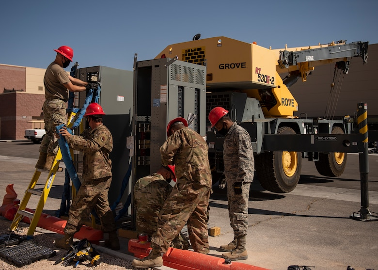 Five RED HORSE Airmen prepare a gearbox to be lifted by a 30-ton crane.