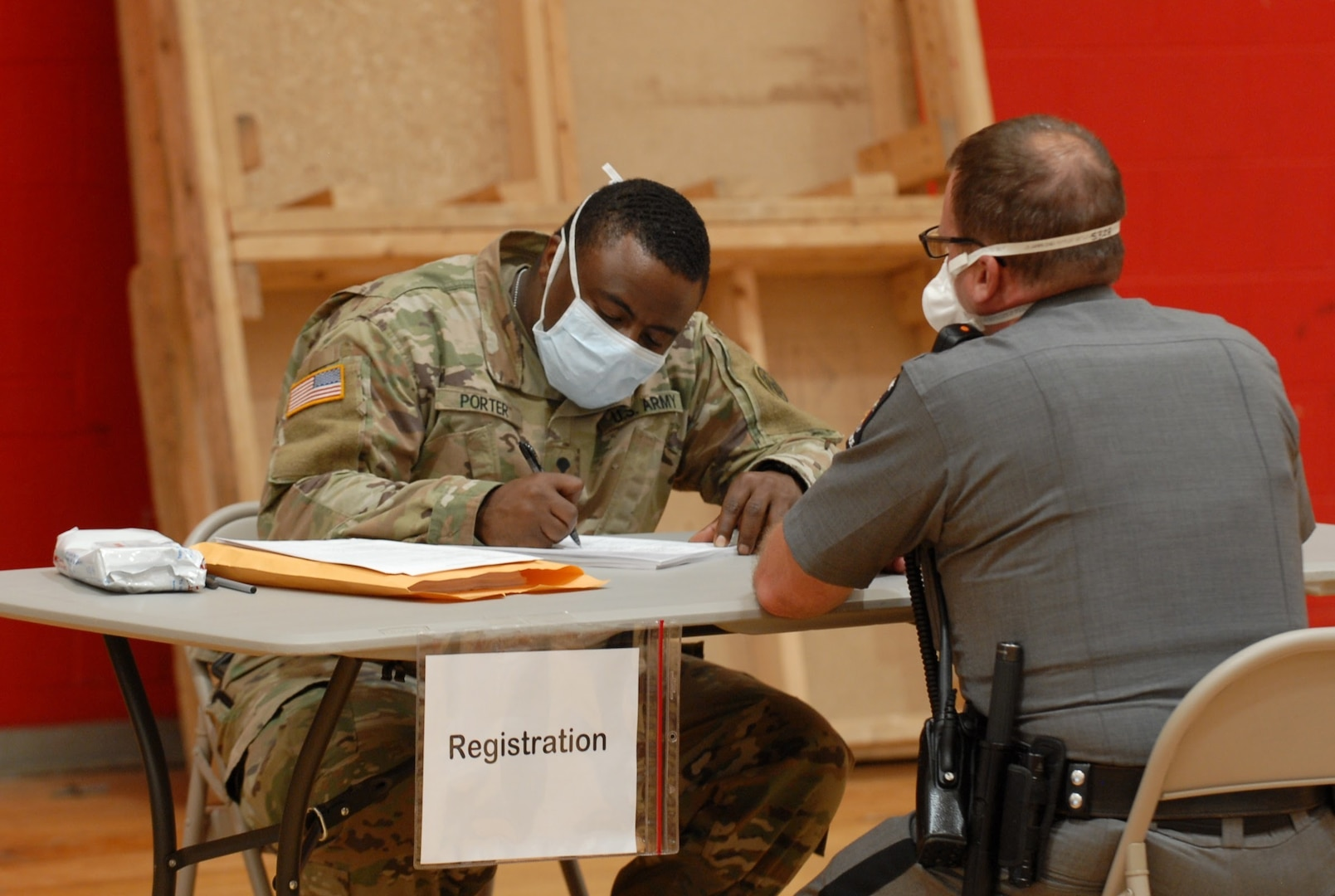 Army National Guard Spc. Matthew Porter, assigned to D Company, 427th Brigade Support Battalion, collects information from a member of the New York State Police at a COVID-19 antibody testing site in Williamsville, New York, May 5, 2020. Wedgwood and other members of the New York National Guard are supporting state agencies at antibody testing sties across New York.