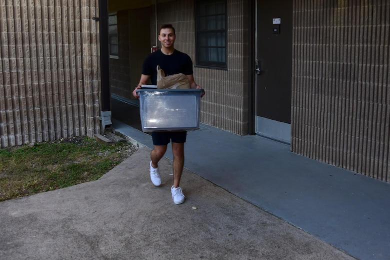 Airman 1st Class Matthew Blasberg, 47th Healthcare Operations Squadron referral management and patient travel technician, walks down from his dorm room with a container of cooking supplies, May 5, 2020 at Laughlin Air Force Base, Texas. For Blasberg, the trouble of cooking five or so meals at a time is well-worth the effort because of the time it saves him time in the long run. (U.S. Air Force photo by Senior Airman Anne McCready)