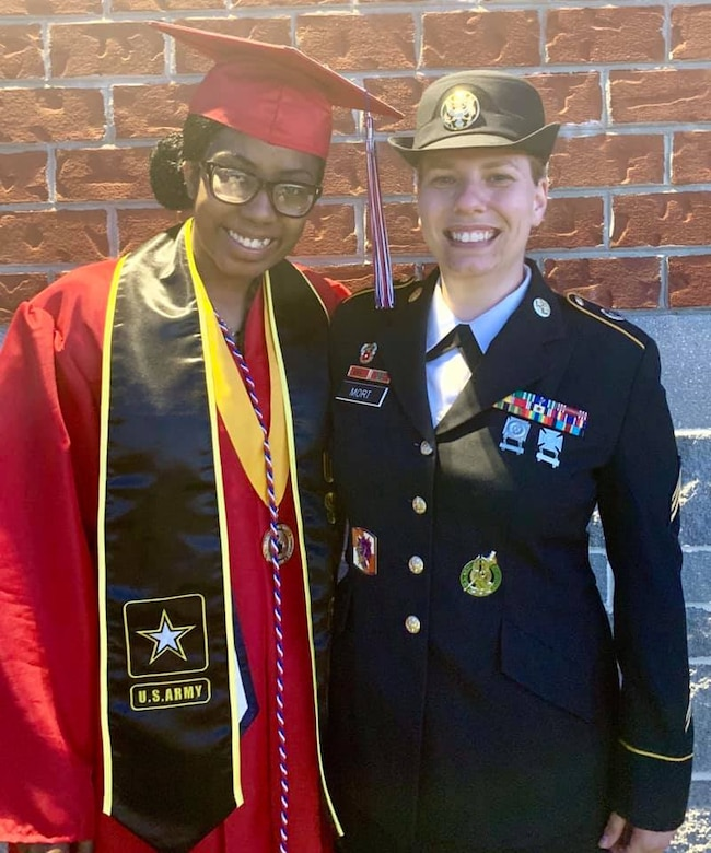 Future Soldier dressed in graduation cap and gown poses with female Soldier, Sgt. Mort, who is wear her Army dress uniform.