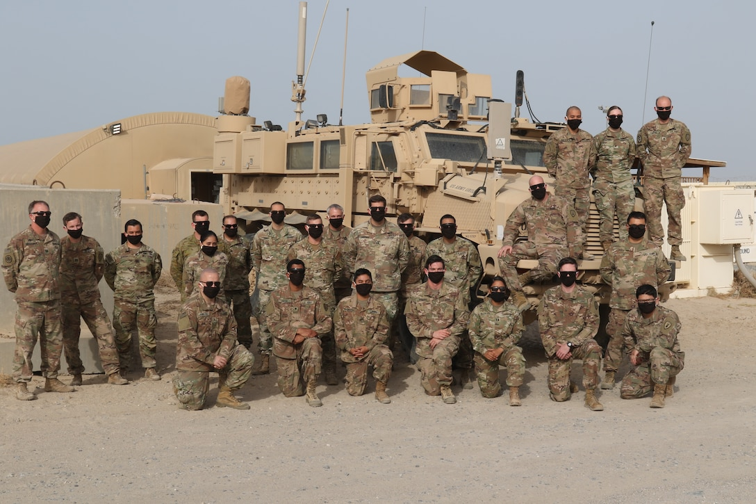 Service members from the U.S. and Australia stand together while wearing masks made for them, by Annette Frye on May 8, 2020 in Kuwait. Annette is mother of EOD technician Master Sgt. Ronnie Brickey, part of Task Force Hellhound in Kuwait.