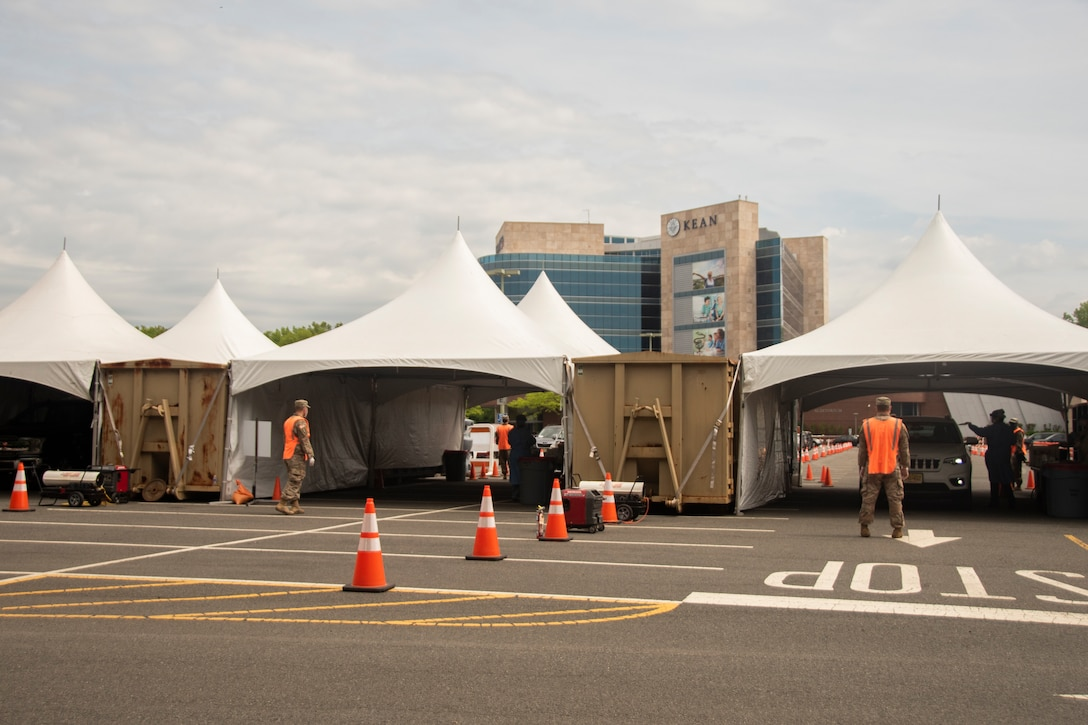 Soldiers from the New Jersey National Guard stand in front of drive-through, specimen collection tents at the Union County COVID-19 testing site located at Kean University in Union, N.J., May 18, 2020.  The NJNG is working with Union County to provide security and traffic control at Kean University. (U.S. Air National Guard photo by Senior Airman Julia Santiago)