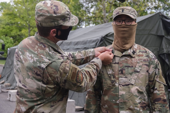 U.S. Air Force Col. John Cosgrove, 108th Wing commander, left, pins captain ranks on 1st Lt. Jiahua Ye during a promotion ceremony at the Union County COVID-19 testing site located at Kean University in Union, N.J., May 18, 2020. Ye is serving as the officer in charge of the testing site and is responsible for ensuring the Guardsmen's needs are met in order to accomplish the mission. (U.S. Air National Guard photo by Senior Airman Julia Santiago)