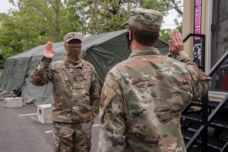 U.S. Air Force 1st Lt. Jiahua Ye, left, recites the Officer's Oath during a promotion ceremony at the Union County COVID-19 testing site located at Kean University in Union, N.J., May 18, 2020.  Ye is serving as the officer in charge of the testing site and is responsible for ensuring the Guardsmen's needs are met in order to accomplish the mission. (U.S. Air National Guard photo by Senior Airman Julia Santiago)