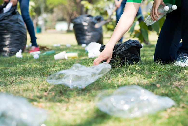 Photo shows a close up of hands picking up trash off grass.