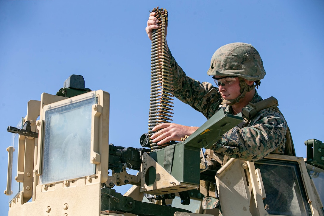 A U.S. Marine loads 7.62 mm ammunition into an M240B machine gun during a live-fire range part of a field exercise at Camp Lejeune, North Carolina, May 7, 2020.