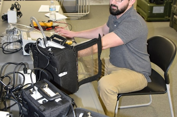 Dean Edwards, a contractor working as a Biomedical Equipment Technician (BMET) from MMOD-Tobyhanna, tests aspirator machines during a maintenance trip to assist a Maryland National Guard unit in February. MMOD-Tobyhanna is one of three regional Medical Maintenance Operations Divisions operated by the U.S. Army Medical Materiel Agency, a direct reporting unit to Army Medical Logistics Command.