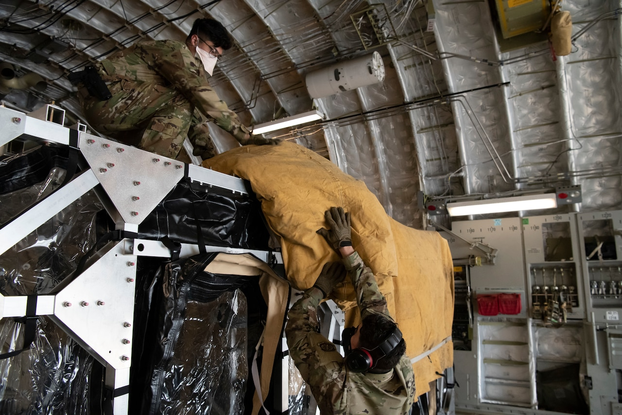 Airmen cover a Transport Isolation System with a tarp.