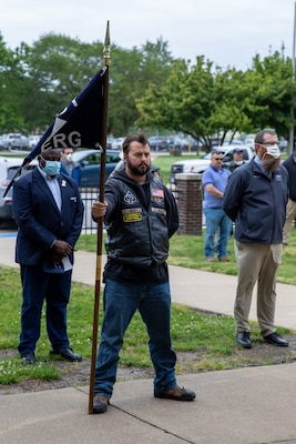 Norfolk Naval Shipyard (NNSY) Veteran Employee Readiness Group (VET-ERG) Information and Awareness Officer Nate Benton stands ready with the VET-ERG flag during the Memorial Day Fall-In for Colors May 19.