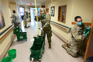 Four North Dakota Air National Guard members wear personal protective equipment as the wipe and mop a hallway using sanitizing liquid at a congregate living facility Fargo, N.D., May 18, 2020.