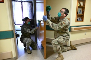 Photo of two North Dakota Air National Guard members wiping both sides of a door with sanitizing fluid at a congregate living facility Fargo, N.D., May 18, 2020.