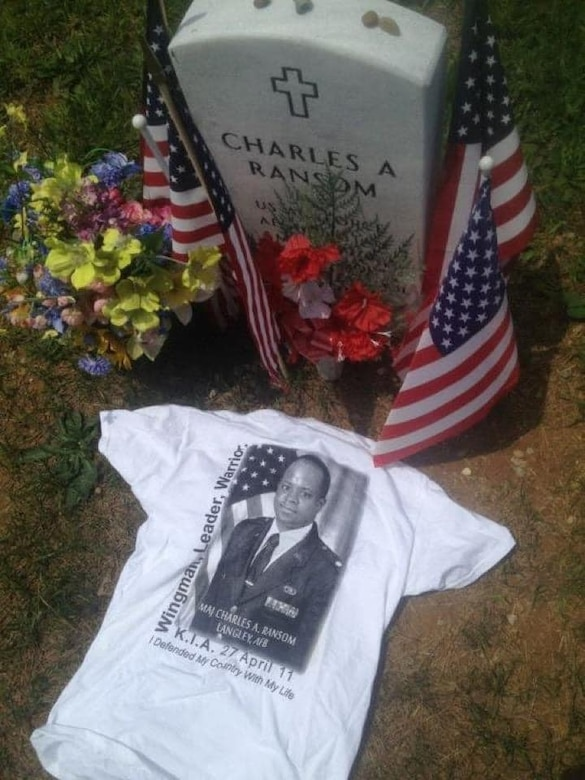 The grave of Major Charles Ransom, flight commander of plans and operations, 83rd Network Operations Squadron, is decorated with flowers, flags and a shirt that says, Wingman, Leader, Warrior, which is part of the Airman's Creed. Ransom made the ultimate sacrifice April 27, 2011. (Courtesy photo)