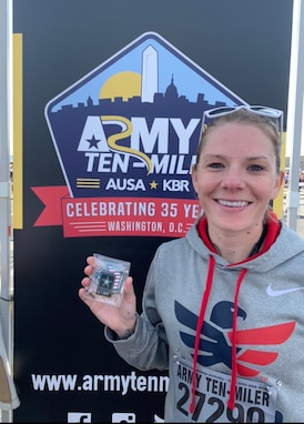 Soldier wearing a hoodie poses with her medal in front of an Army Ten Miler poster.