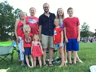 Two grandparents, a husband and wife and their four kids smile wearing red, white and blue at a 4th of July Ceremony.