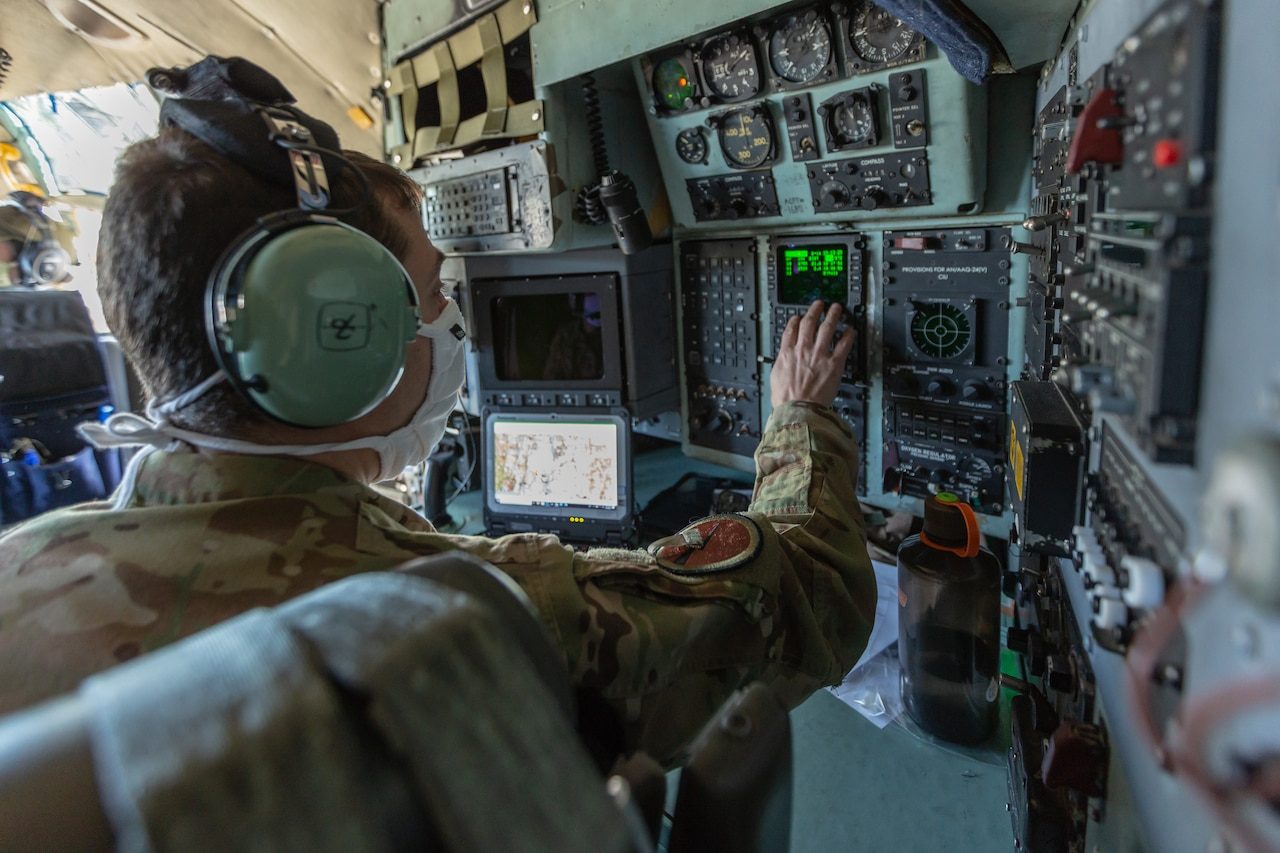 A man in a military uniform interacts with a computer system in the cockpit of an aircraft.