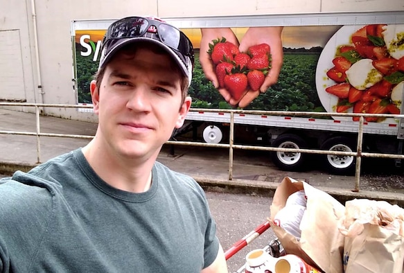 A Caucasian male stands in front of a food delivery truck along with paper bags filled with supplies.