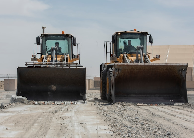 Airmen use heavy equipment to clear debris from runway.