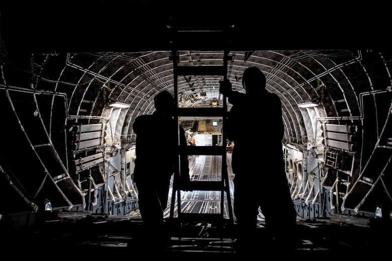 Senior Airman Zach Smith and Airman 1st Class Luke Morrow, 911th Maintenance Squadron crew chiefs, set up a ladder inside a C-17 Globemaster III during a Home Station Check inspection at the Pittsburgh International Airport Air Reserve Station, Pennsylvania, May 10, 2020.