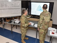 Col. Scott Coradi (left) and Col. Jon Farr discuss operational plans while overlooking a map of the area of operations for Pennsylvania Task Force South at Horsham Air Guard Station, Pennsylvania, on May 2, 2020.
