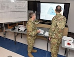 Col. Scott Coradi, left, and Col. Jon Farr discuss operational plans while overlooking a map of the area of operations for Pennsylvania Task Force South at Horsham Air Guard Station, Pennsylvania, May 2, 2020.