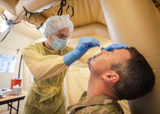A medic wearing pushes a testing swab into a soldier's nose