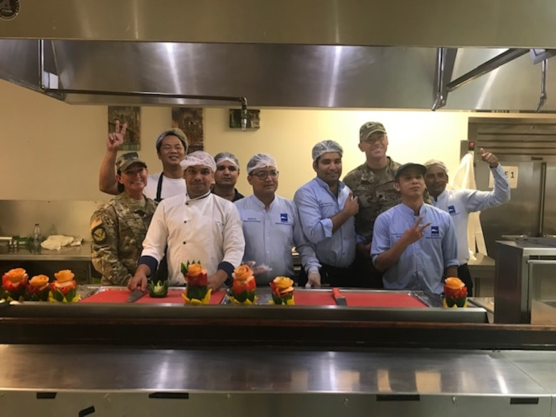 Members with the 379th Expeditionary Force Support Squadron pose for a photo prior to serving Thanksgiving dinner in Nov. 28, 2019, at Al Udeid Air Base, Qatar.