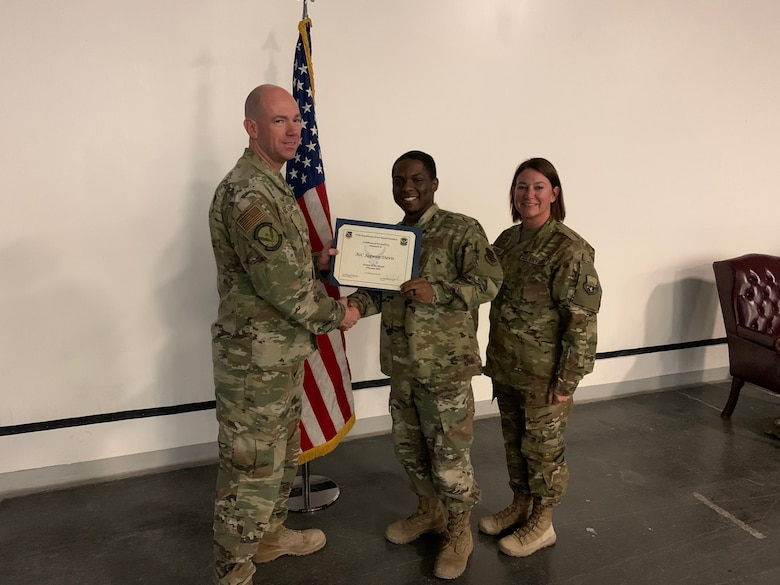 The 379th Expeditionary Force Support Squadron Commander Lt. Col. Sean Brazel and Chief Master Sgt. Marty Arnold congratulate Airman First Class Jaqwan Davis for winning Airman of the Month in February, 2020 at Al Udeid Air Base, Qatar. (Courtesy photo)