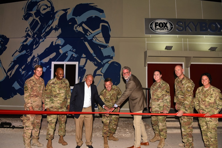 Brig. Gen. Daniel Tulley, 379th Air Expeditionary Wing commander, Larry Jones FOX Sports executive vice president and Gary Hartley, executive vice president, graphics, and creative director and 379th AEW leadership members cut the ribbon for the FOX Sports Skybox grand opening at Al Udeid AB, Qatar on Aug. 10, 2019. (U.S. Air Force photo by Staff Sgt. Ashley L. Gardner)