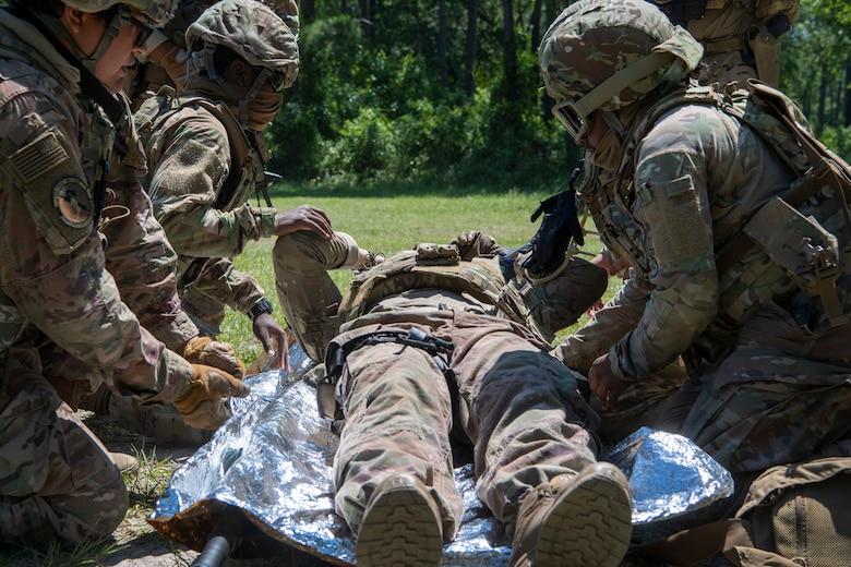 Airmen treat a patient during a training scenario