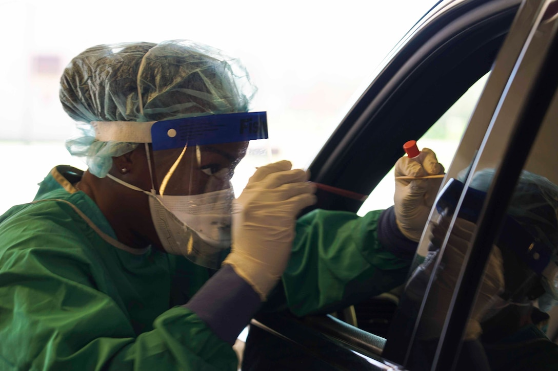 An airman wearing personal protective equipment leans into a car holding a swab and a test tube.