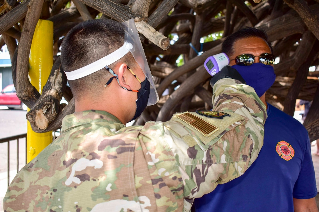 An airman wearing personal protective equipment checks a man's temperature.