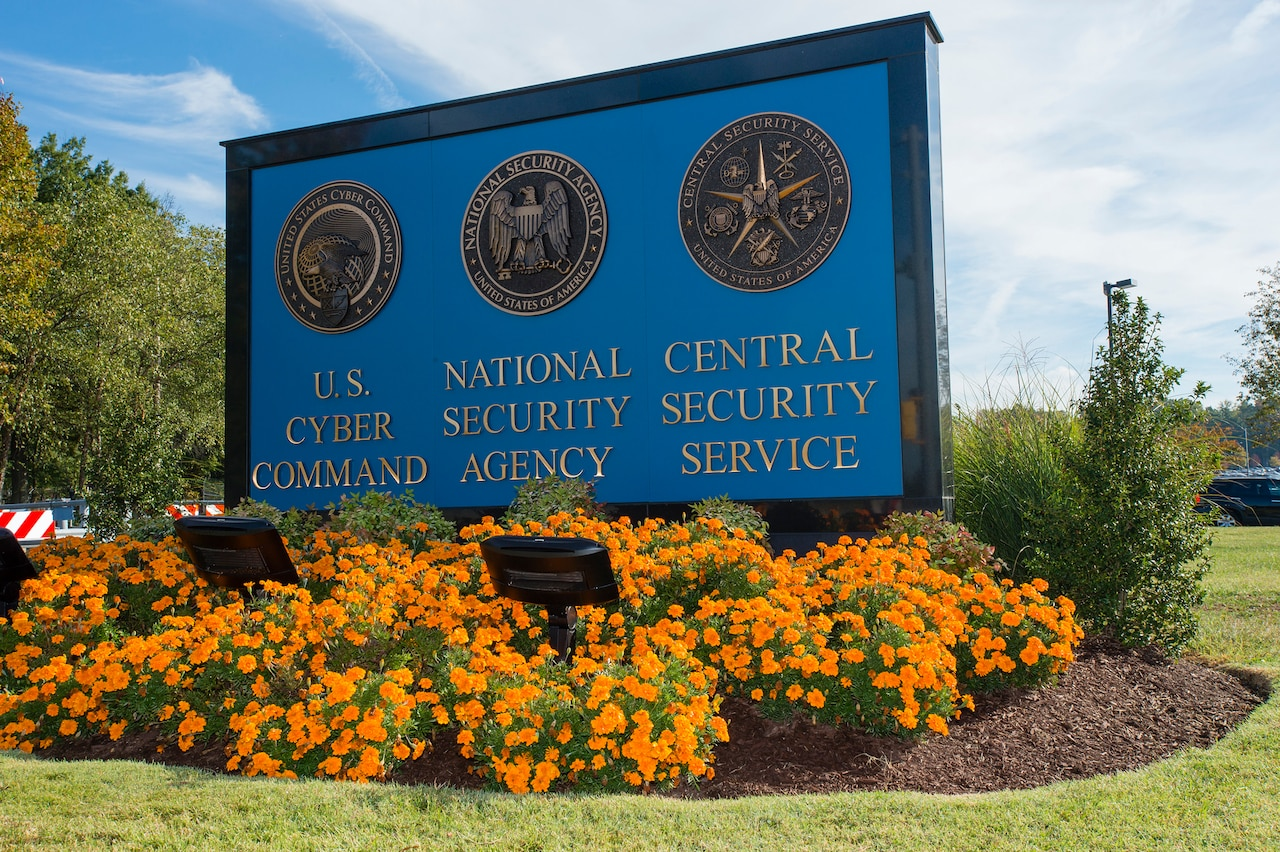 "Three seals are affixed to an outdoor sign that identifies each seal:  ""U.S. Cyber Command,"" ""National Security Agency,"" and ""Central Security Service."" Brightly colored flowers bloom around the sign.."