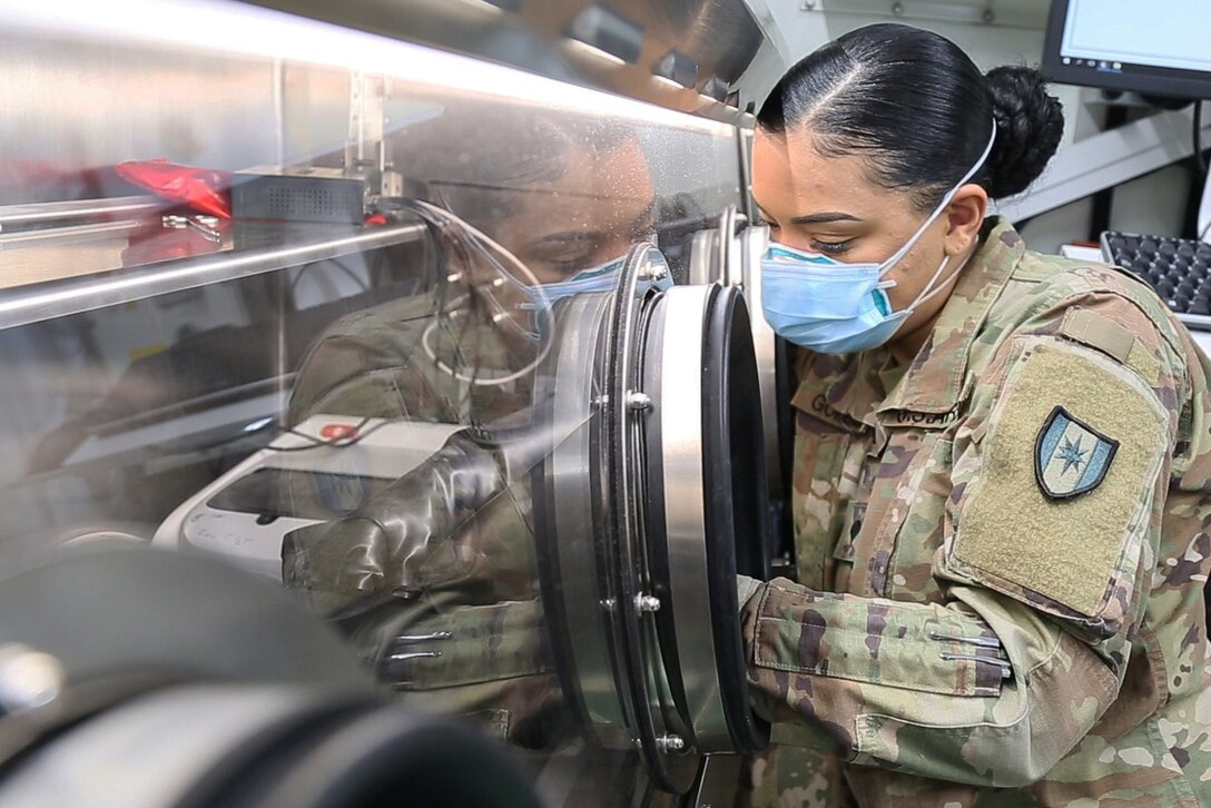 A soldier uses a mobile lab system to conduct a coronavirus test.