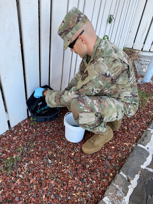 Senior Airman David Walker, 647th Civil Engineer Squadron pest management journeyman, refills the rodent bait stations around a building on Joint Base Pearl Harbor-Hickam, Hawaii, May 19, 2020. The bait attracts rodents to ensure the team can catch the pests before they enter JBPHH buildings. (Courtesy photo)