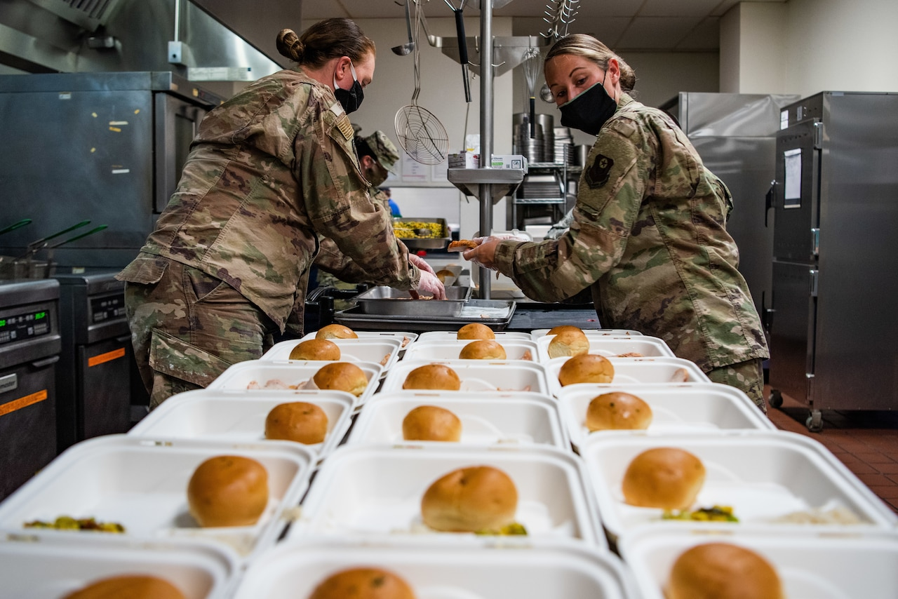 Airmen prepare meals for quarantined airmen.