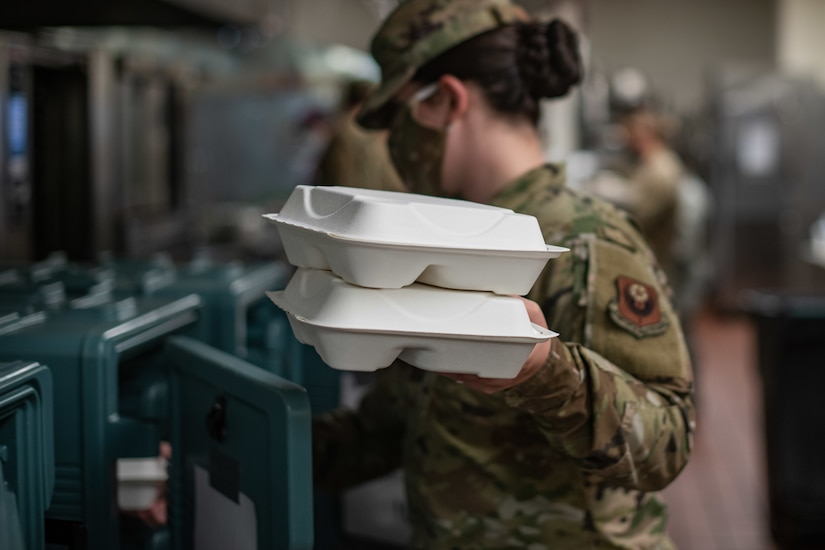 An airman prepares food for quarantined airmen.
