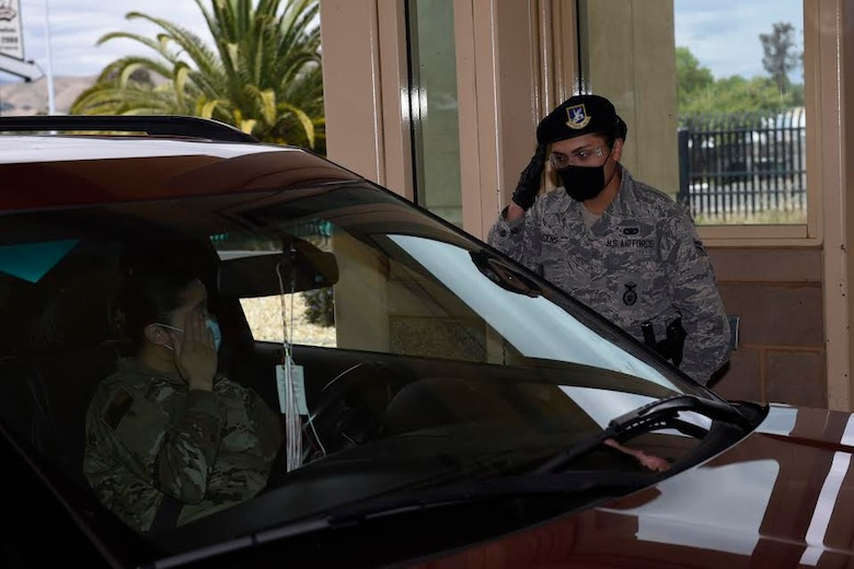 U.S. Air Force Airman 1st Class Hannah Hoskins, 60th Security Forces Squadron entry controller, salutes an officer May 11, 2020, at the main gate of Travis Air Force Base, California. Security forces Airmen manning entry control points at Travis AFB are required to wear protective equipment such as masks and gloves to prevent exposure to the coronavirus. (U.S. Air Force photo by Airman 1st Class Cameron Otte)